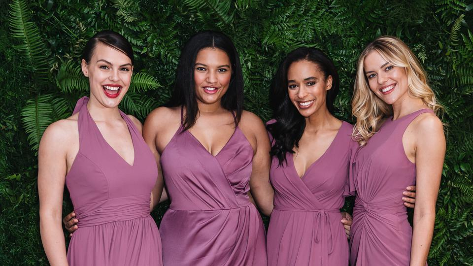 A photo of four models wearing bridesmaid dresses in different styles but the same color