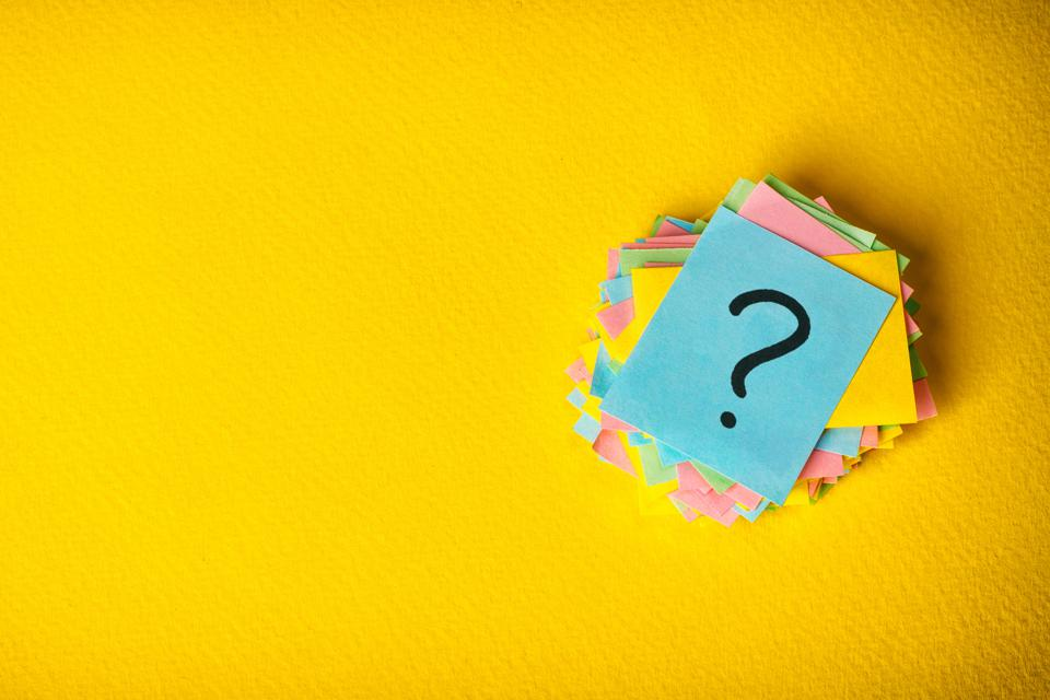 Stack of post-it notes with a question mark written on them, with a bright yellow background
