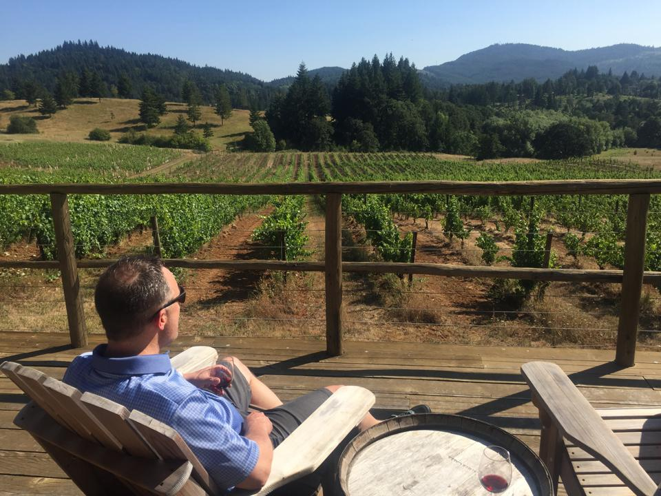A man enjoys a glass of wine on the deck at Lumos Wine Co.