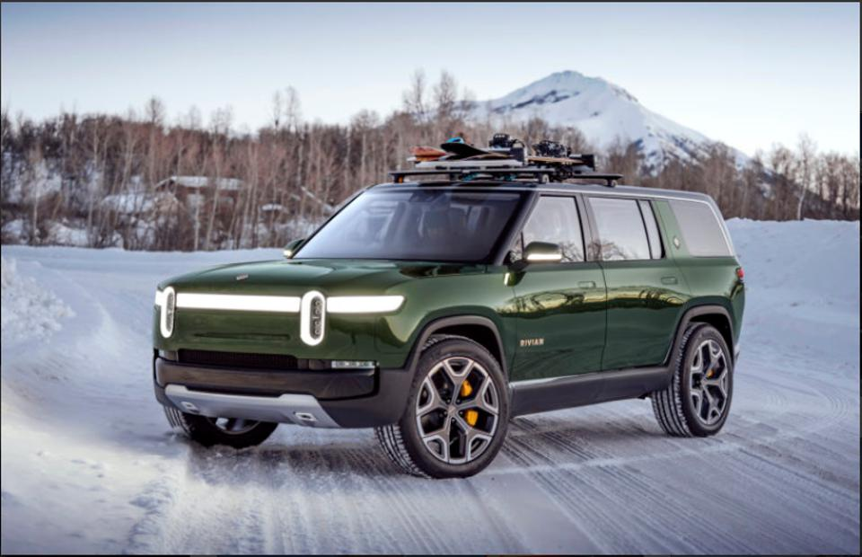 Green Rivian RS1 electric SUV in a snowy mountainscape.
