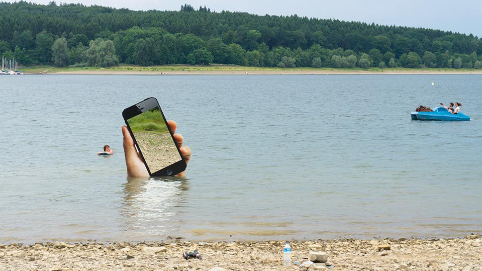 A hand holding a phone while drowning in lake at a tourist site.