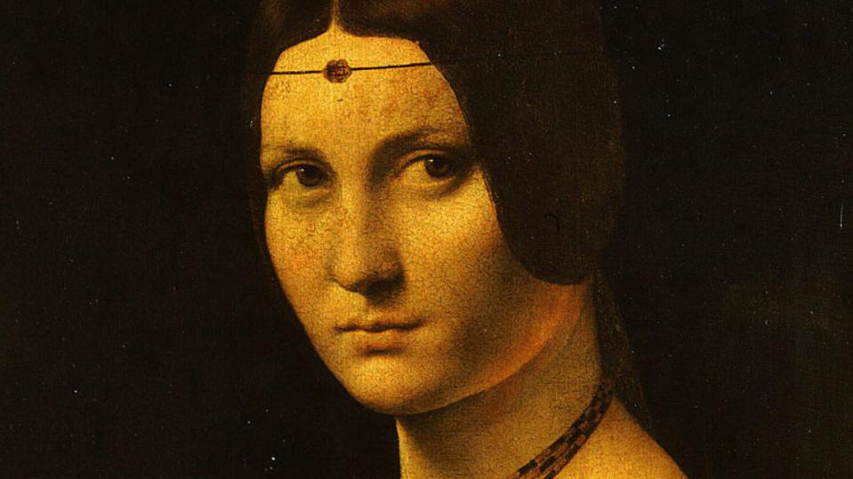 A woman with a golden complexion wearing a head jewel and looking meekly to the left in a painting by Leonardo da Vinci.