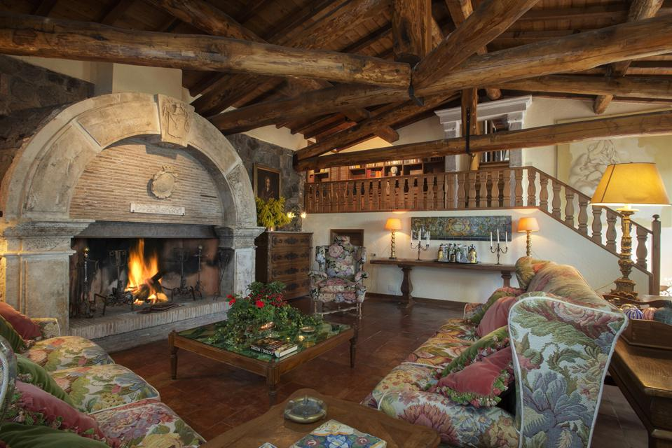The estate features wood-beamed ceilings and oversized stone fireplaces.