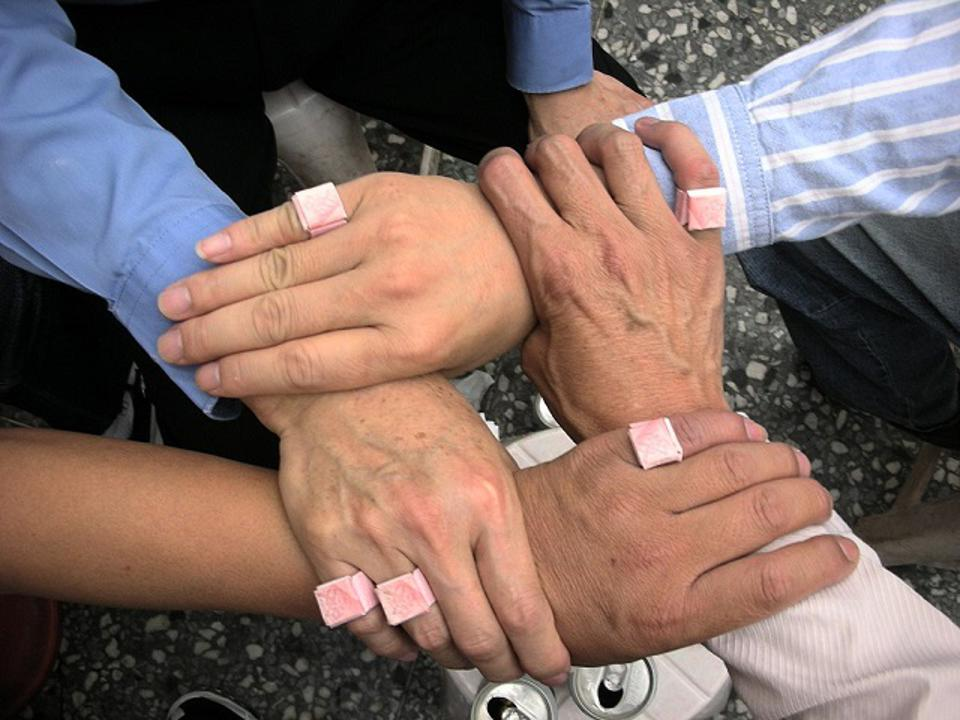 Four male and female hands and forearms placed together in a four-way bond to signifyunity and partnership.