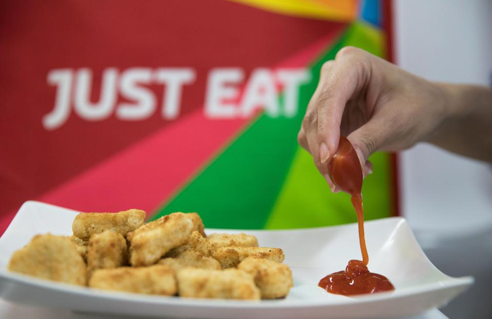 A hand squeezing a Nopla condiment capsule of ketchup onto a plate of nuggets