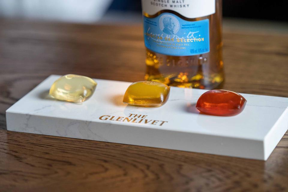 Three edible capsules containing whisky cocktails in front of a bottle of The Glenlivet whisky