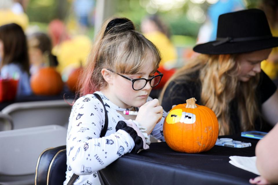 A child enjoys making her own pumpkin art at Newfield's inaugural Harvest Fest.