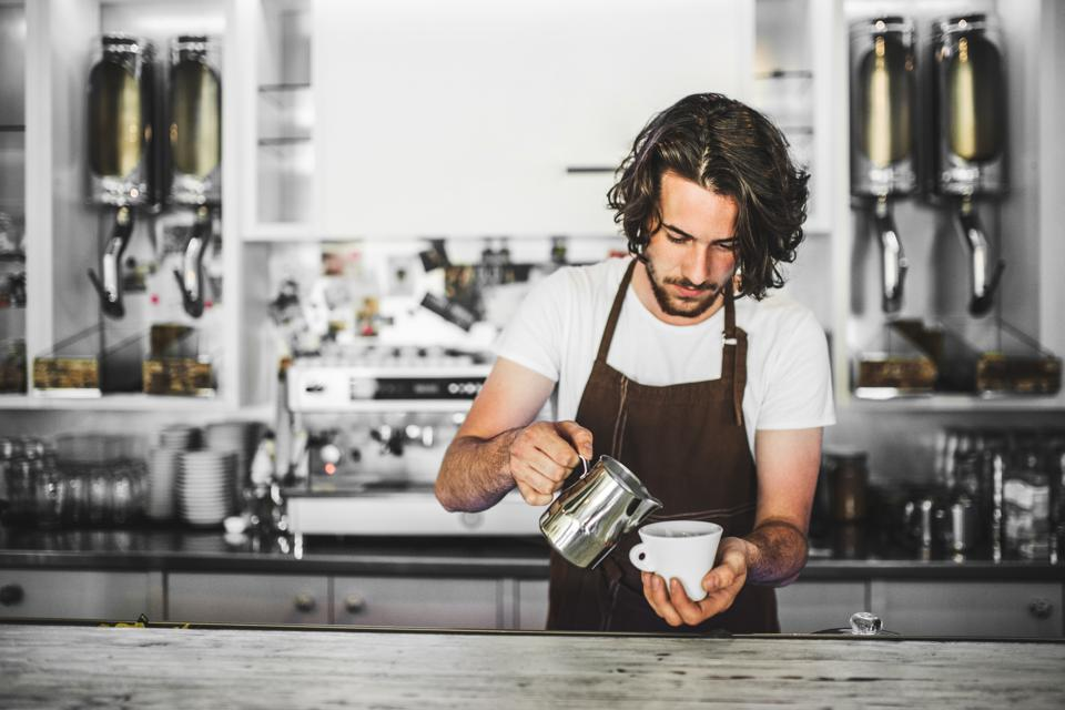 A professional barista working in a cafe, preparing coffee. Copy space.