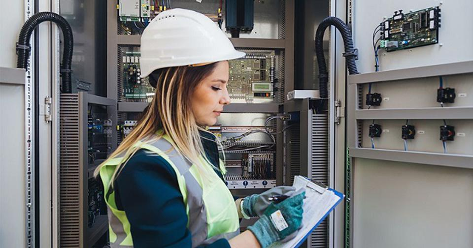 A female field service management engineer working on a engineering system and looking at a clipboard.