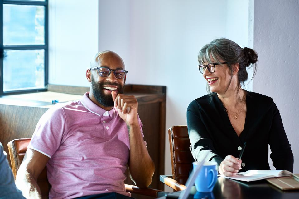 Cheerful mature businesswoman laughing with male coworker