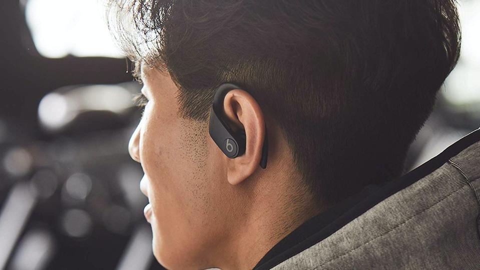 Person wearing black Beats Powerbeats Pro headphones.