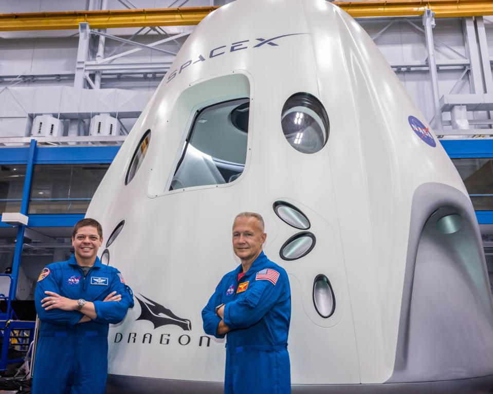Astronauts Bob Behnken (left) and Doug Hurley pose in front of a SpaceX Crew Dragon.