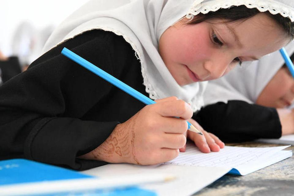 A young student practices her penmanship in her new UNICEF notebook at the Bibi Amina Girls High School in Panjshir, a province in northern Afghanistan.