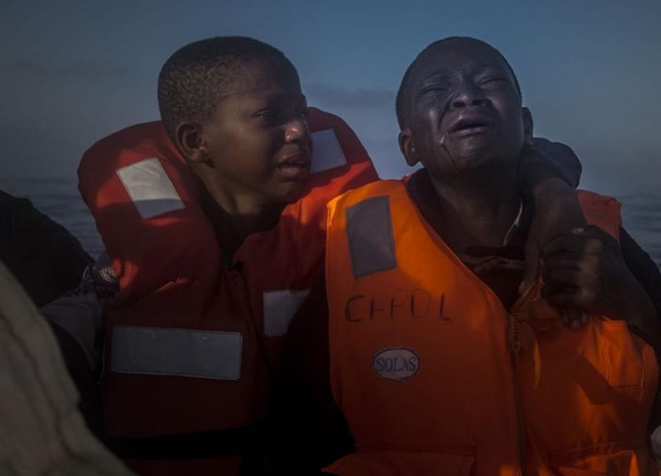 An 11-year-old girl from Nigeria (left) comforts her younger brother aboard a rescue boat after they were picked up from an overcrowded dinghy in the Mediterranean Sea0 en route to Italy, about 14 miles north of Sabratha, Libya, on July 28, 2016. Their mother died in Libya, after crossing the Sahara.