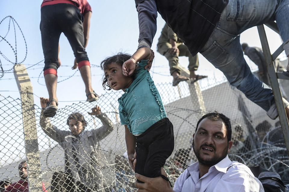 People cross into Turkey from Syria through a broken fence near the official border crossing at Akçakale on June 14, 2015.