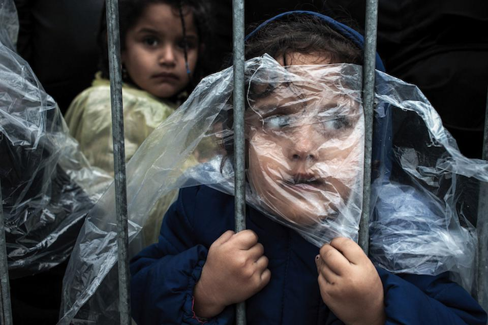 Refugee children covered by rain ponchos wait in line to be registered in Preševo, Serbia on October 7, 2015.