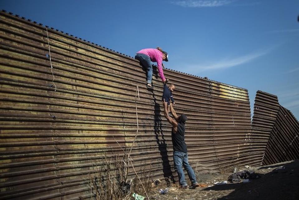 Central American migrants climb the border fence between Mexico and the United States, near El Chaparral border crossing, Tijuana, Baja California, Mexico, on November 25, 2018.