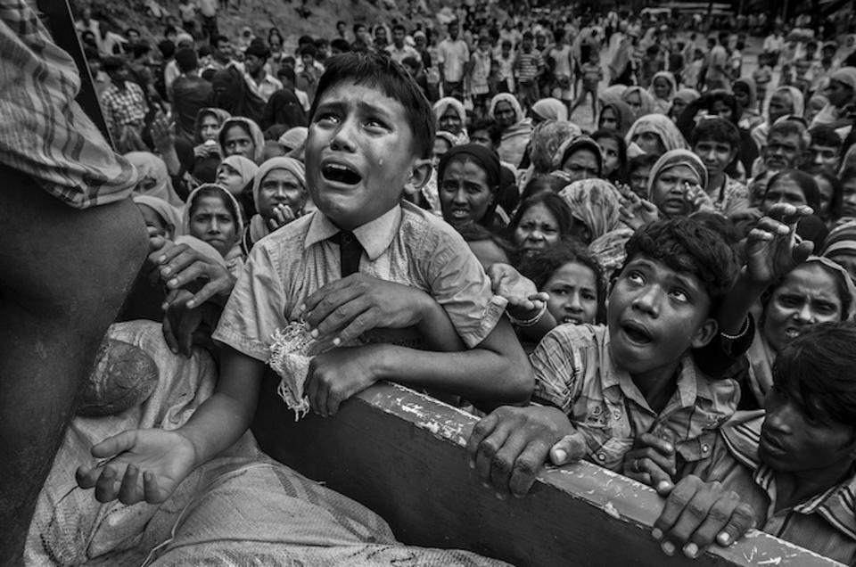 A young Rohingya refugee cries as he climbs on a truck distributing aid near the Balukhali refugee camp in Cox's Bazar, Bangladesh on September 20, 2017.