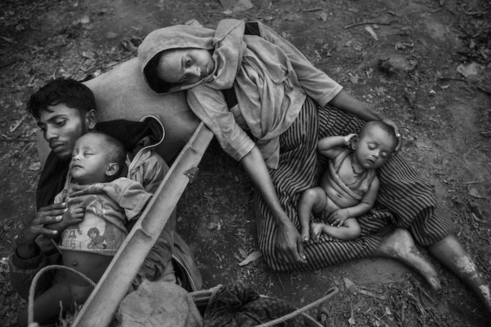 On October 2, 2017, Minara Hassan, her husband, Ekramul, and their children lie exhausted on the ground on the Bangladesh side of the Naf River, after fleeing their home in Maungdaw, Myanmar.