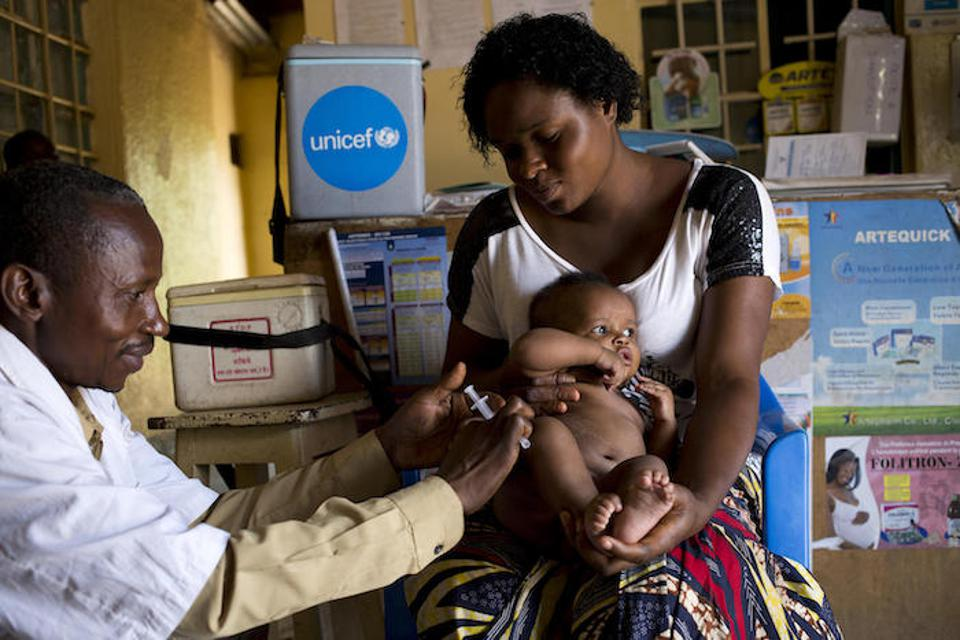 In November 2018, health worker Lsiri Lowoso vaccinates 3-month-old Zoe against measles, rubella, tetanus and polio as his mom, Arellete Ytshika, holds him at the Centre de Sante le Rocher Maternity Hospital in Lubumbashi, DRC.