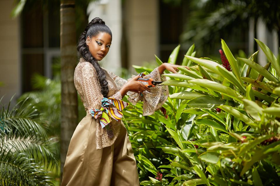 An African woman in an African dress inspired by French Revolutionary fashion in a garden