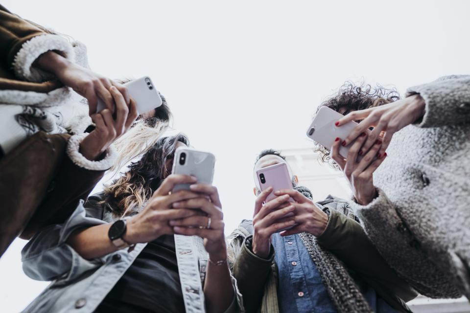 Group of friends in the street with smartphone