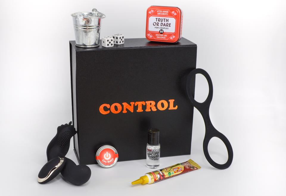 A Kink Kit subscription box with its contents laid out around it