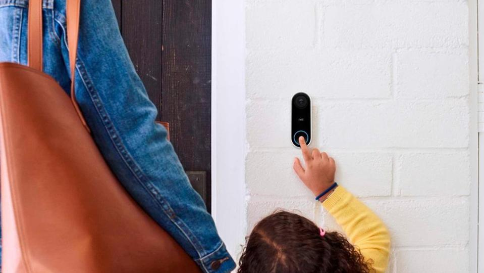 Person pressing the button on a Nest Hello doorbell mounted to a white wall.