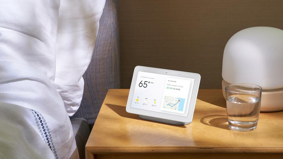 Google Nest Hub on a nightstand next to a glass of water.