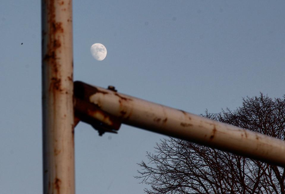 A waxing gibbous moon between rugby posts.