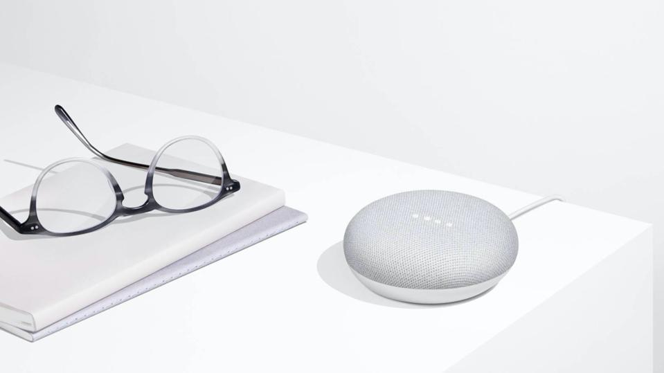 Grey Google Home Mini on a white table next to glasses and a notebook.