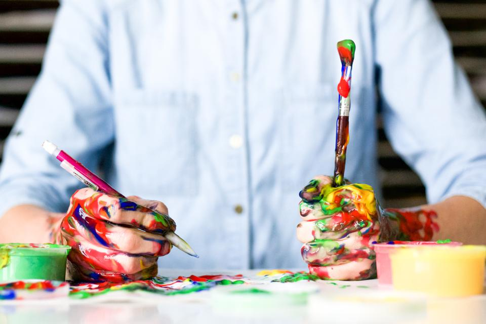 A marketer holds a pencil and paintbrush.