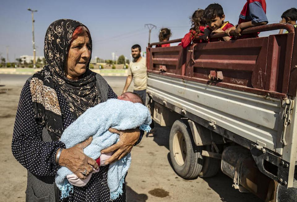 A grandmother cradles a baby near a transport of Syrian Arab and Kurdish in Tall Tamr town, in the Syrian northwestern Hasakeh province on October 10, 2019.