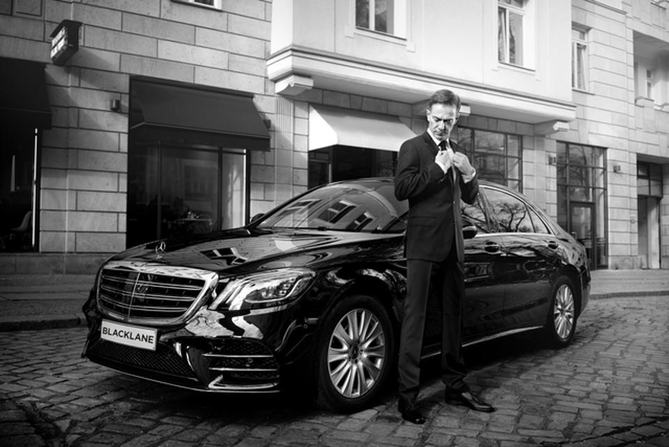 A chauffeur awaits their client.