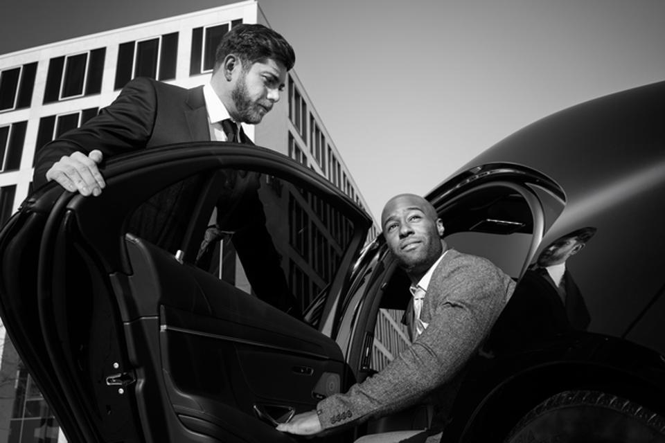 A Chauffeur holds the door for their client.