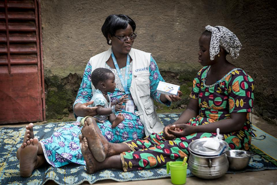 Marietta Mounkoro, a nutrition officer based at the UNICEF field office in Sikasso, Mali, visits with a mother in Zebala village to discuss how micronutrient powders can be used to fortify her baby's food.