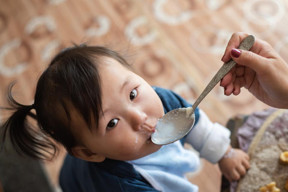 A child in Ulaanbaatar, Mongolia, is given porridge mixed with micronutrient powders to ensure proper nourishment, which prevents stunting and cognitive delays.