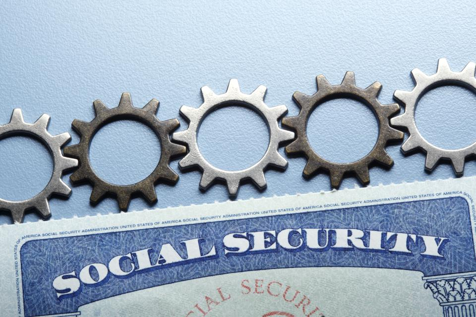 Gears Resting On Top Of Social Security Card