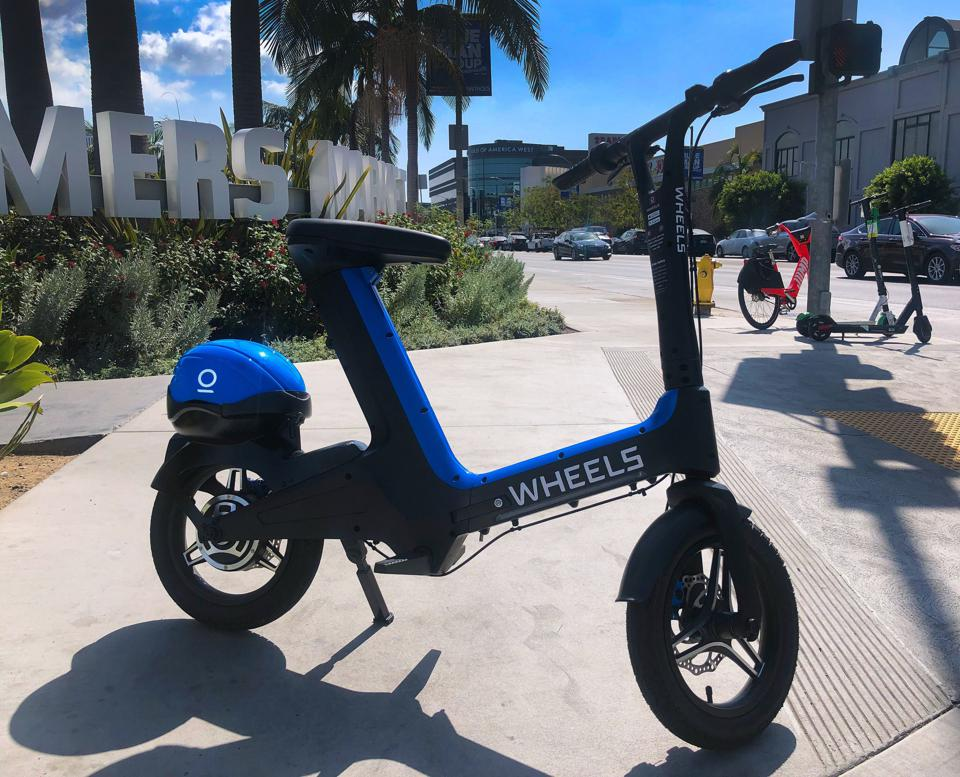 A compact blue, electric bike with 14″ wheels with a bike helmet mounted on the fender.