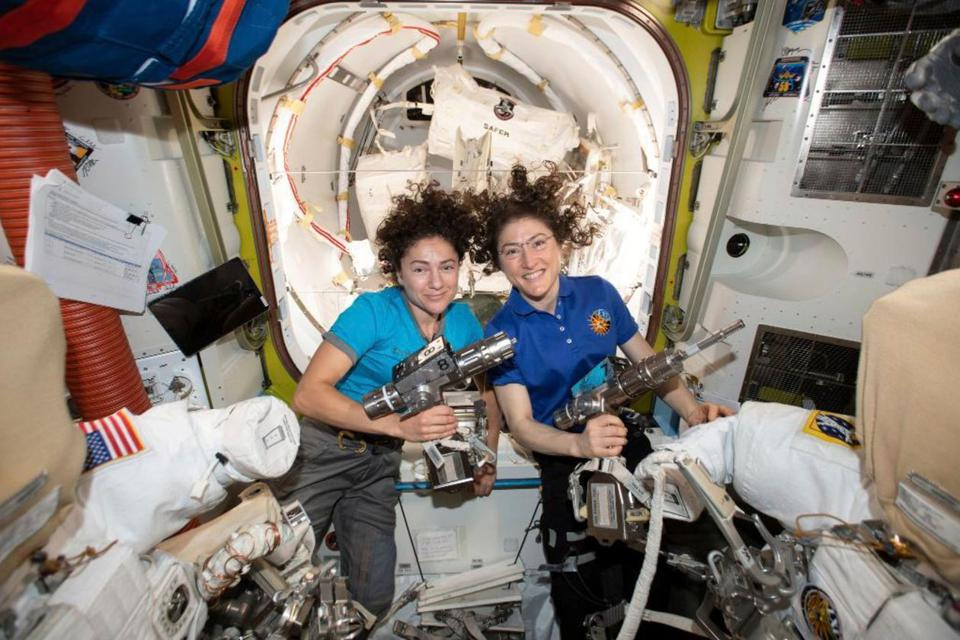 Astronauts Jessica Meir, left, and Christina Koch brandish power tools on board the ISS.