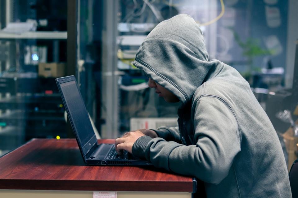 Hacker is Using Computer for Organizing Massive Data Breach Attack on Corporate Servers. Their Hideout is Dark