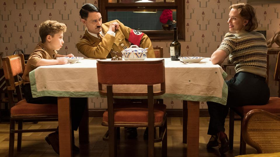 JOJO RABIT. (From L-R): Jojo (Roman Griffin Davis) has dinner with his imaginary friend Adolf (Writer/Director Taika Waititi), and his mother, Rosie (Scarlet Johansson). Photo by Kimberley French.