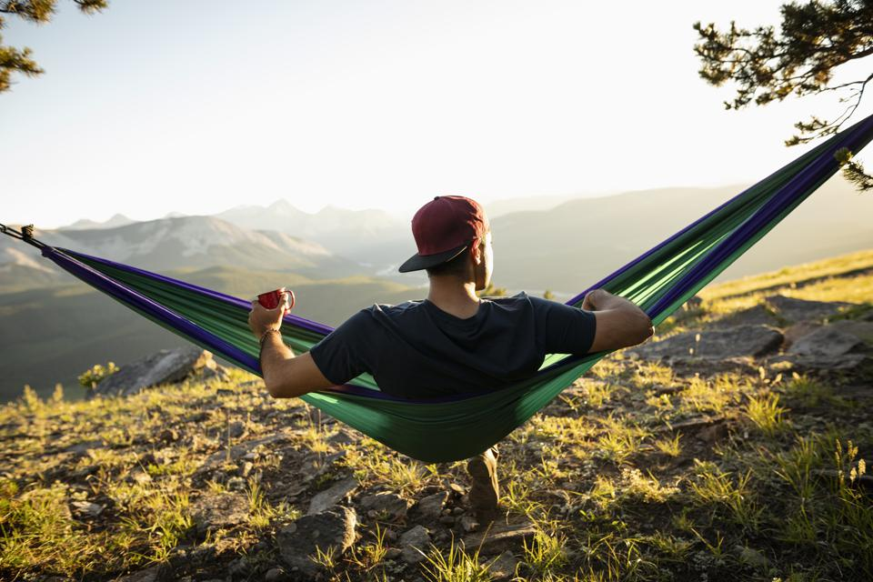 Serene man drinking coffee in sunny hammock with idyllic mountain view, Alberta, Canada
