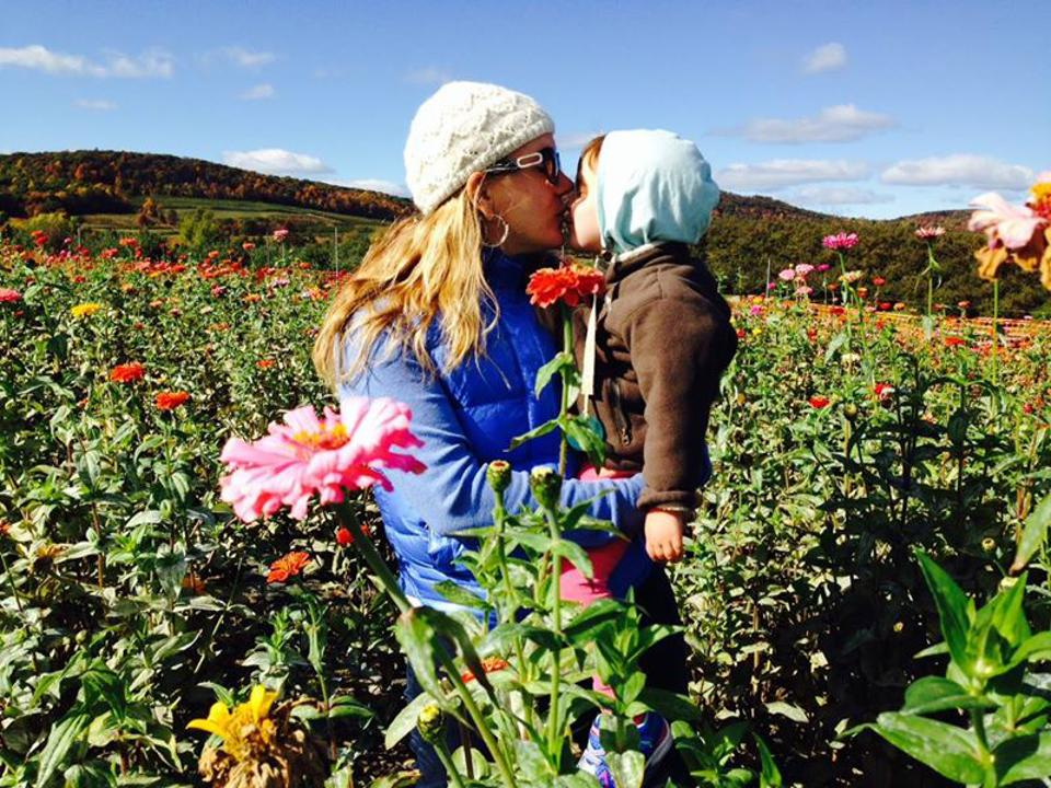 Rope kisses her daughter in a field of flowers.