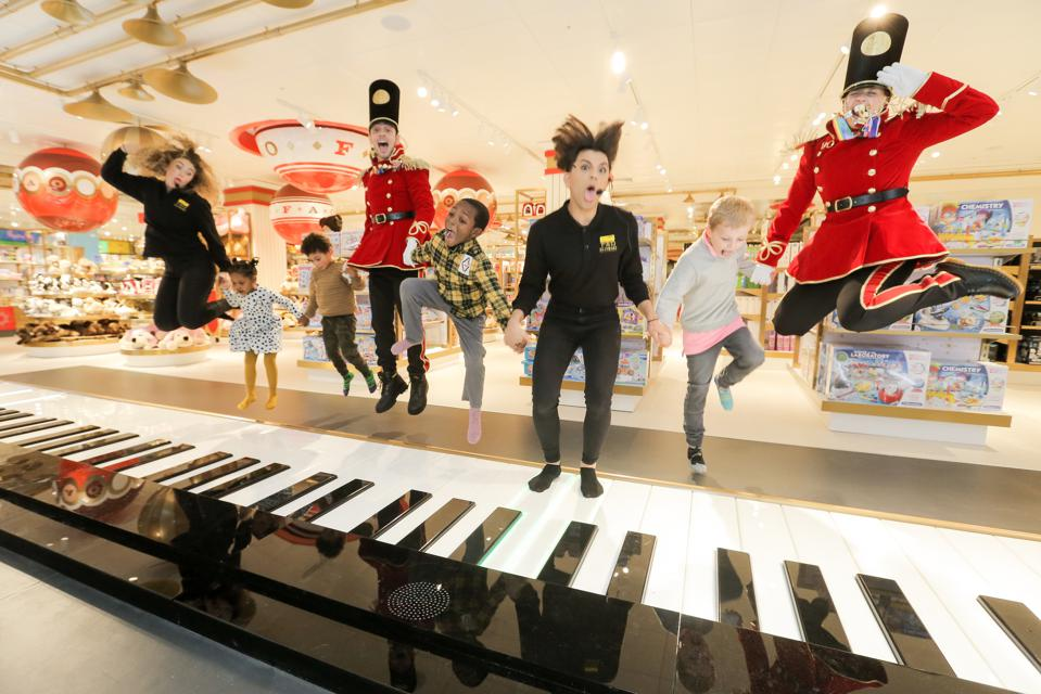 Kids, costumed toy soldiers, and store employees dance on the walk-on piano keyboard st the new FAO Schwarz in London.
