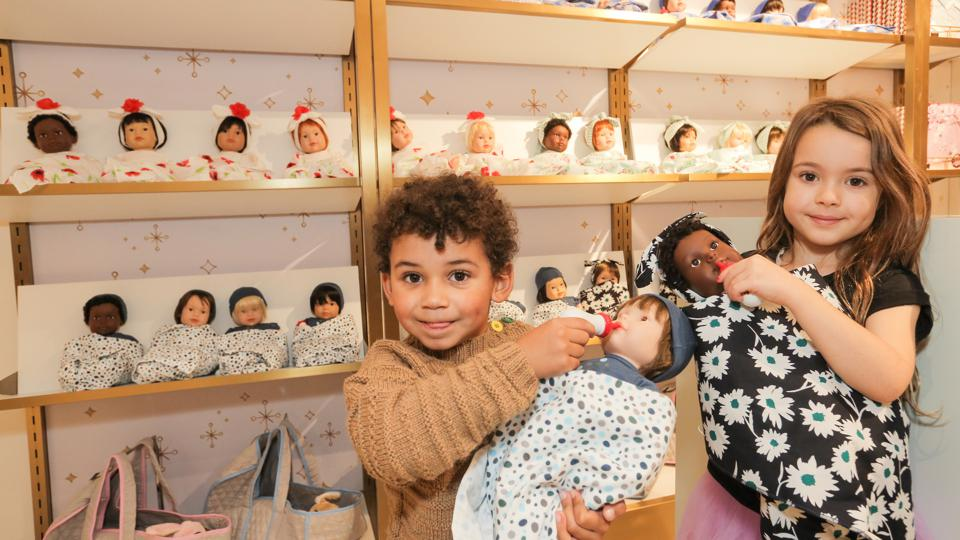 Two chidren playing with baby dolls at the FAO Schwarz store that opened October 22 in London in Selfridges on Oxford Street.