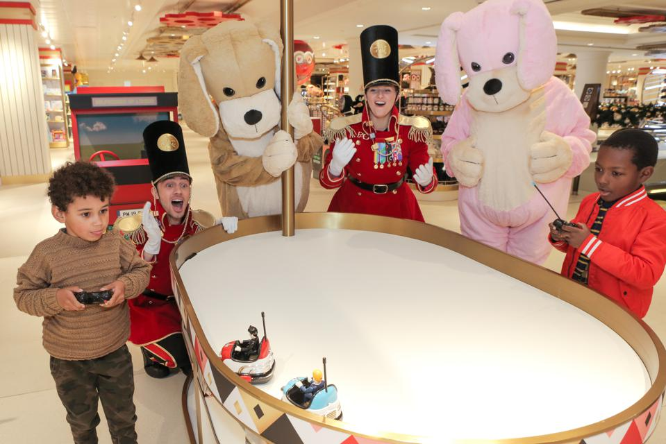 Children and costumed FAO Schwarz employees at the remote control car play station at the new store in London.