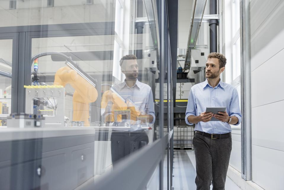 Businessman checking robots with digital tablet in high tech company