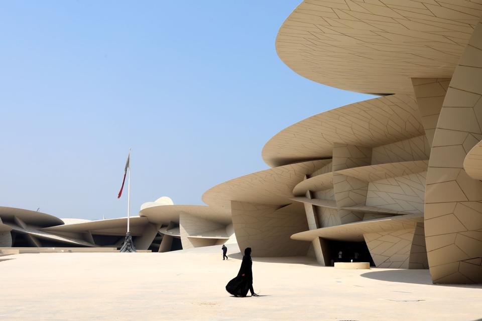A local woman walks through the main courtyard of the National Museum of Qatar