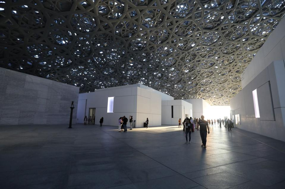 Visitors walk through the grounds of the Louvre Abu Dhabi in the UAE capital on 12 January 2018